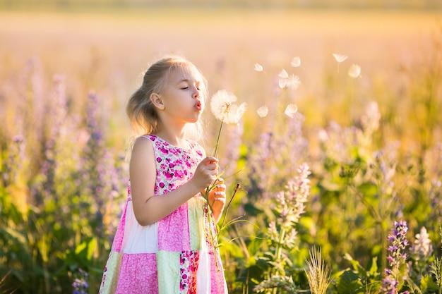 O retrato da menina loura no campo da flor no por do sol.