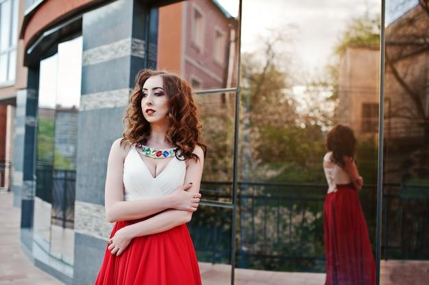 O retrato da menina na moda no vestido vermelho levantou a janela do espelho de fundo do edifício moderno