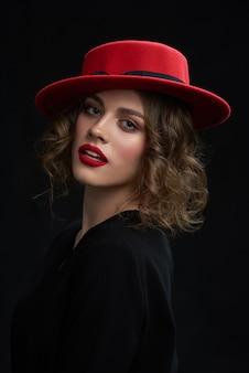 O retrato da moça bonita, batendo o batom vermelho, dia compõe e chapéu vermelho elegante.