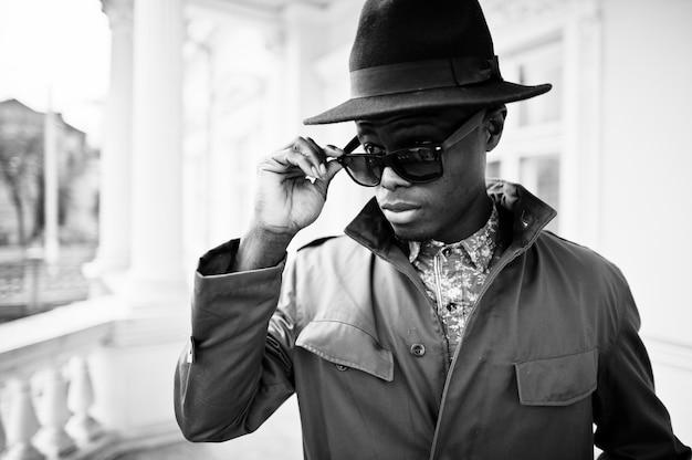 O retrato da moda do homem afro-americano preto na capa do casaco verde e chapéu preto, fica na varanda da mansão amarela. foto em preto e branco