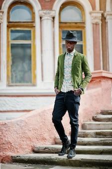 O retrato da moda do homem afro-americano preto no casaco de veludo verde e chapéu preto fica na mansão antiga do fundo de escadas. foto vertical