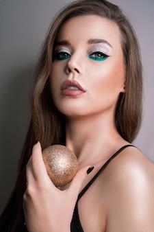 O retrato da modelo com cabelo comprido e pele perfeita em uma bola de natal de fundo cinza na mão