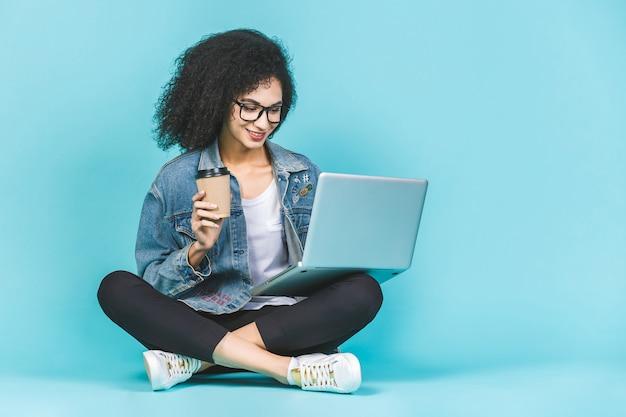 O retrato da mulher afro-americana nova de sorriso que usa o portátil ao sentar-se em um assoalho com pés cruzou-se isolado sobre o fundo azul. beber café ou chá.