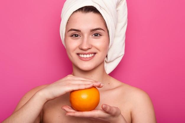 O retrato da mulher alegre atrativa com a toalha branca na cabeça, prende a laranja sobre a parede cor-de-rosa. jovem sorridente mulher visita salão de spa e tem descanso, cuida de sua pele. conceito de beleza natural.