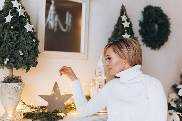 O retrato da mulher alegre feliz nova no natal decorou em casa. natal, felicidade, beleza, apresenta o conceito