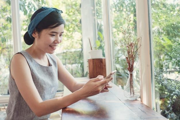 O retrato da mulher asiática 40s envelhecida média saudável que faz a chamada de vídeo facetime com smartphone em casa, usando o zoom que encontra o aplicativo on-line, distanciamento social, trabalha em casa, trabalha remotamente o conceito