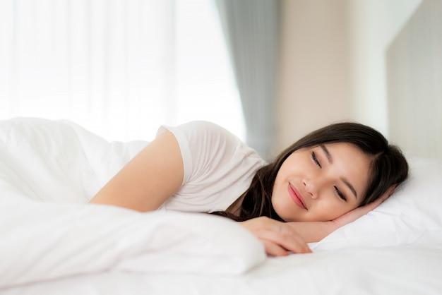 O retrato da mulher asiática bonita com sorriso atrativo aprecia o colchão macio fresco de linho da roupa de cama no apartamento moderno do quarto branco da cama. sono bonito da menina de ásia que descansa, conceito do sono da boa noite.