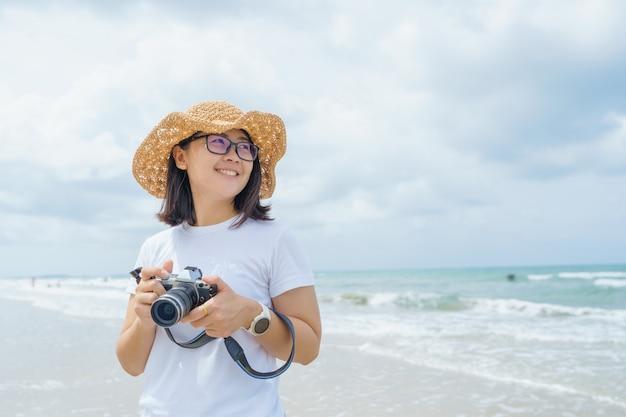 O retrato da mulher asiática bonita nova relaxa ao sol na praia perto do mar.