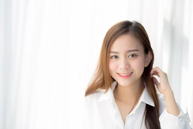 O retrato da mulher asiática bonita que está a janela e sorri quando acorde.
