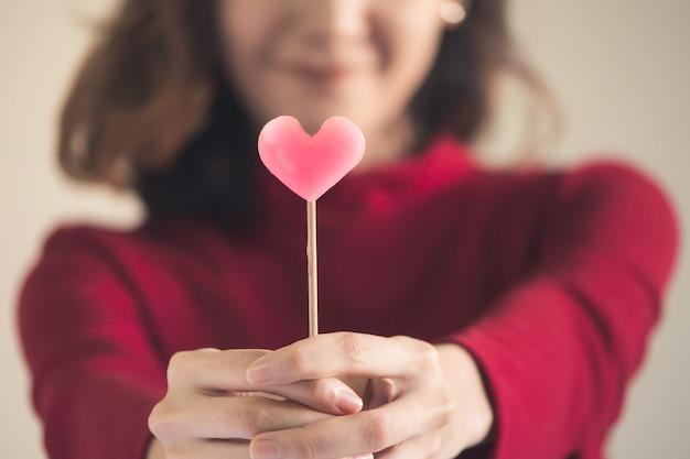 O retrato da mulher asiática feliz vestiu-se na camisola vermelha que prende doces cor-de-rosa do coração.