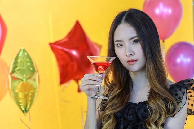 O retrato da mulher asiática nova bonita de sorriso que guarda o copo de vinho tinto com parede amarela e colore o balão completo.