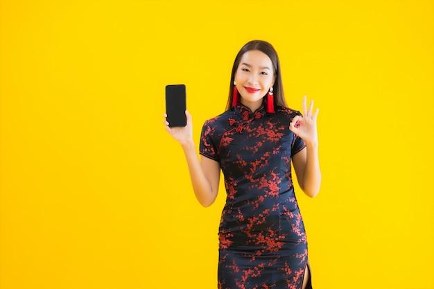 O retrato da mulher asiática nova bonita veste o vestido chinês e usa o telefone de smartmobile