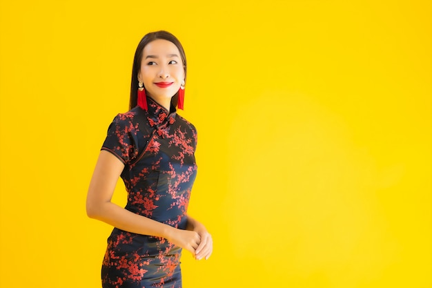 O retrato da mulher asiática nova bonita veste o vestido e sorrisos chineses