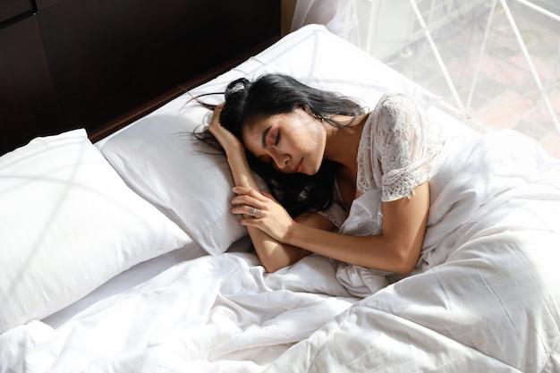 O retrato da mulher asiática nova e bonita que veste a roupa de noite branca da roupa de dormir dorme no quarto. cabelo comprido jovem bonito deitado na cama e acordar tarde. conceito de estilo de vida