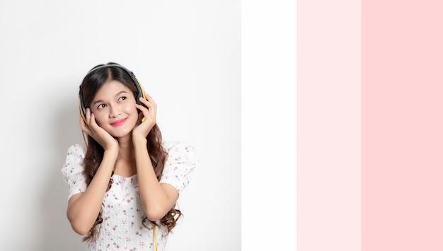 O retrato da mulher asiática nova feliz põr sobre fones de ouvido escuta a música, menina tailandesa de sorriso bonita.