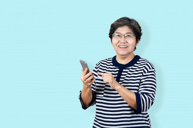 O retrato da mulher asiática superior feliz que guarda ou que usa o smartphone e que olha a câmera no fundo isolado que sente positivo aprecia e satisfação. fundo fêmea azul do conceito do estilo de vida mais velho.