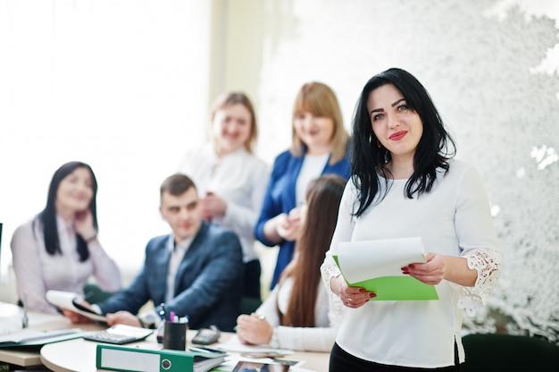 O retrato da mulher caucasiano na blusa branca mantém o dobrador verde contra os executivos do grupo de trabalhadores de banco.