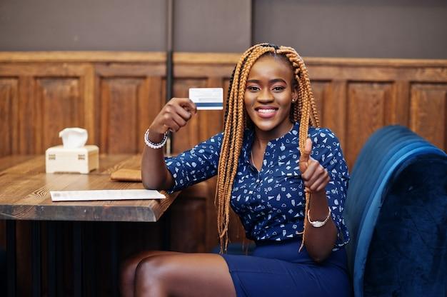 O retrato da mulher de negócios africana nova bonita, veste a blusa azul e a saia, sentando-se no restaurante e mantém-se o cartão de crédito disponivel. ela aparece polegar para cima.