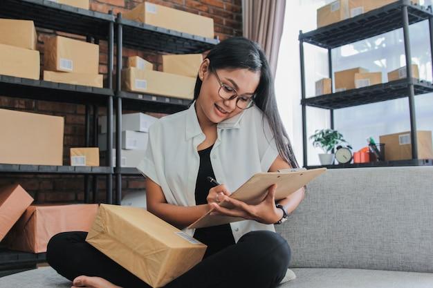 O retrato da mulher de negócios asiática com smartphone trabalha em casa