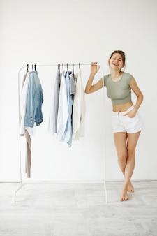 O retrato da mulher feliz bonita nova que sorri estando os ganchos próximos com veste-se sobre a parede branca.