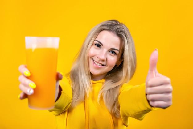 O retrato da mulher loura nova bonita que guarda o vidro do suco de laranja, mostra os polegares acima, assina aprovado à câmera, menina de sorriso isolada.