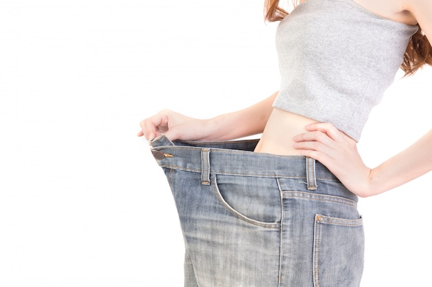 O retrato da mulher mostra a perda de peso vestindo calças de brim velhas, mulher no branco. peso, perda, magro. dieta. copyspace.