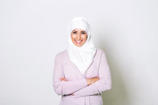 O retrato da mulher muçulmana árabe consideravelmente nova no lenço principal sorri.