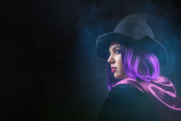 O retrato da mulher no traje de halloween com brilhante compõe e cabelo roxo nas sombras em um preto.