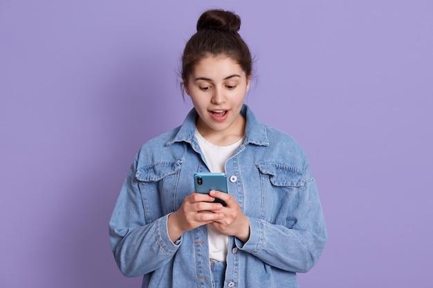 O retrato da mulher surpreendida com o telefone esperto moderno nas mãos, veste a roupa à moda, olhando a tela do telefone móvel com expressão espantada, isolada sobre a parede lilás.