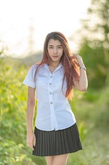 O retrato da universidade asiática ou tailandesa do estudante a menina bonita uniforme relaxa e sorri