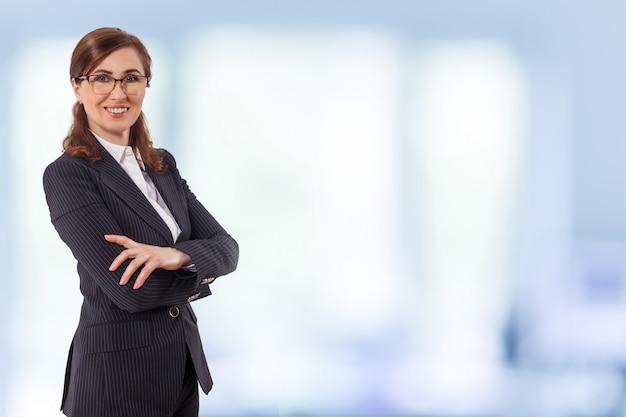 O retrato das orelhas bonitas de uma mulher de negócios 50 velhas nos braços cruzados levanta no escritório.