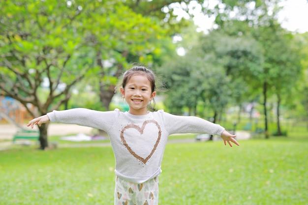 O retrato de crianças asiáticas pequenas de sorriso abriu suas mãos no jardim verde.