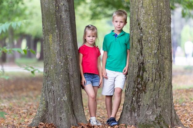 O retrato de duas crianças consideravelmente bonitos menino e menina que estão perto do tronco de árvore grande no verão estaciona fora.