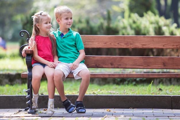 O retrato de duas crianças consideravelmente bonitos menino e menina que têm o tempo do divertimento em um banco no verão estaciona fora.