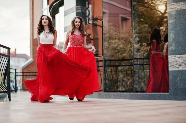 O retrato de duas meninas na moda no vestido de noite vermelho levantou a janela do espelho do fundo do edifício moderno