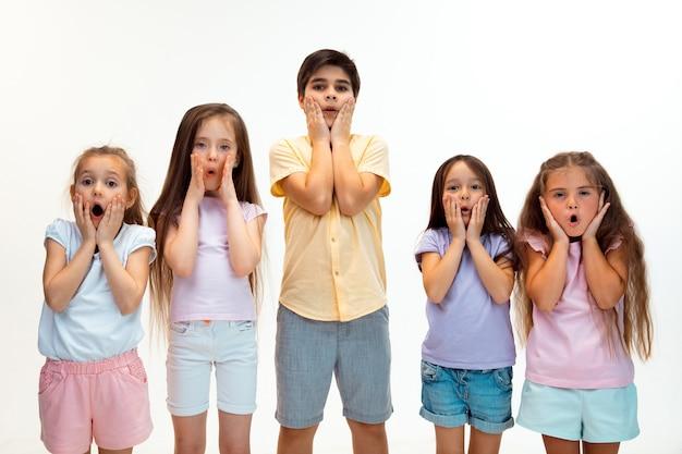 O retrato de felizes fofos crianças menino e meninas em elegantes roupas casuais. moda infantil e conceito de emoções humanas