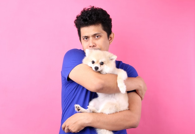 O retrato de homens asiáticos guarda o cão pomeranian com amor e joga com ele no rosa uma parede.