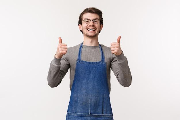 O retrato de jovem positivo animado e animado no avental, trabalhando como barista em uma cafeteria ou barman, mostra os polegares para cima em aprovação, como algo incrível, garante bom gosto