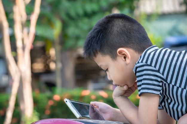O retrato de meninos asiáticos está jogando telefones celulares no parque.