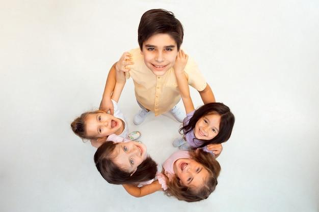 O retrato de meninos e meninas felizes e fofos em roupas casuais elegantes, olhando para cima contra a sala branca