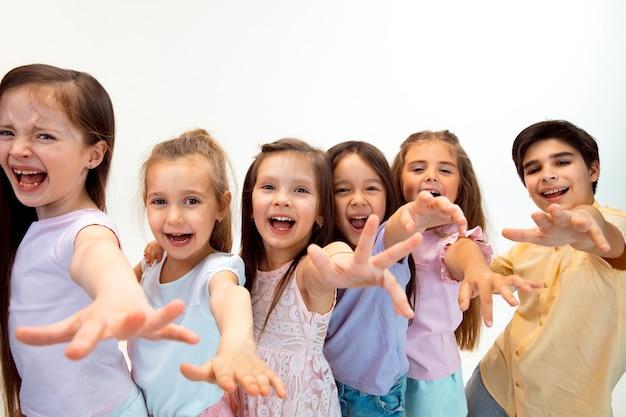 O retrato de meninos e meninas felizes fofinhos em roupas casuais elegantes, olhando para a frente contra a parede branca do estúdio