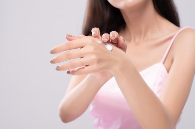 O retrato de mulheres asiáticas usa a loção para o corpo em seus braços. conceito de cuidados com a pele.