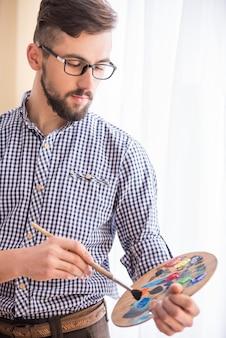 O retrato de um artista masculino novo está misturando o petróleo da cor.
