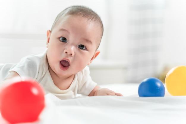 O retrato de um bebê de rastejamento na cama em seu quarto e jogando a bola brinca, bebê adorável no quarto ensolarado branco.