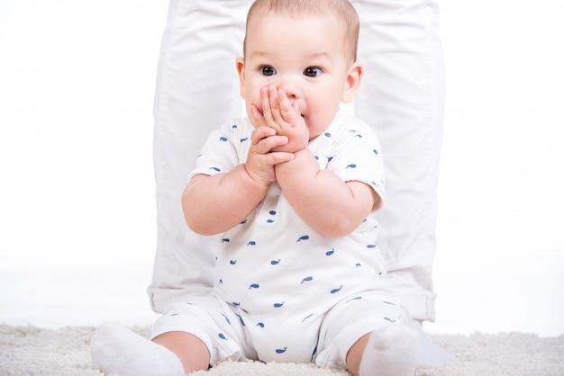 O retrato de um bebê pequeno está sentando-se no assoalho.