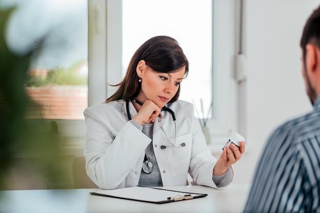 O retrato de um doutor fêmea que guarda o frasco dos comprimidos e escreve a prescrição ao paciente.