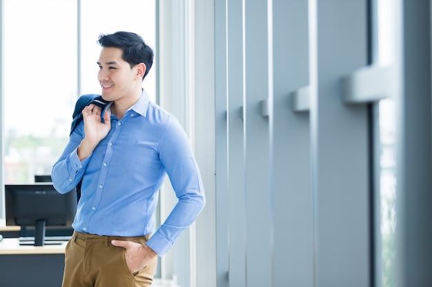 O retrato de um homem de negócios novo asiático maduro alegre veste um terno de negócio do homem no casaco azul e na camisa azul que olha a janela na sala do escritório.