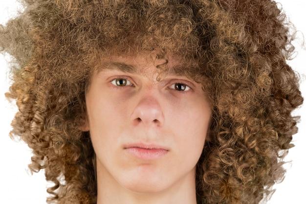 O retrato de um homem europeu encaracolado novo com cabelo encaracolado longo e um olhar desafiante olha no close-up do quadro. cabelo masculino muito exuberante de um cara. um bloqueio de paixão. isolado no fundo branco