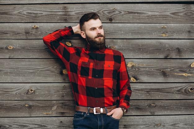 O retrato de um homem farpado à moda novo vestiu-se acima nas calças de brim e em um preto verdadeiro do trabalhador pela camisa vermelha.
