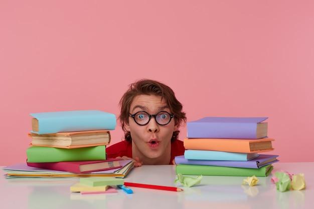 O retrato de um homem feliz espantado de óculos usa uma camiseta vermelha, se escondendo na mesa com os livros, olha para a câmera com expressão de surpresa, parece alegre, isolado sobre o fundo rosa.